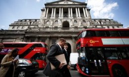 Workers pass the Bank of England building